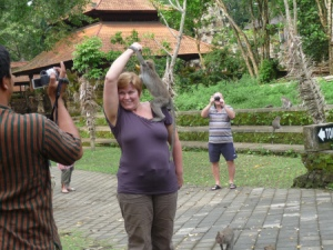 This woman was luring the wild monkeys to climb up her body to get a banana she was holding above her head!