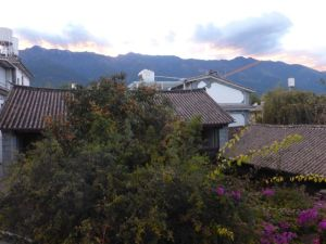 Sunset over the mountains outside Dali.  The tree is loaded with clementines.