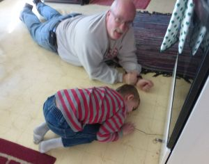 Mike and Kegan searching for treasure under the refrigerator
